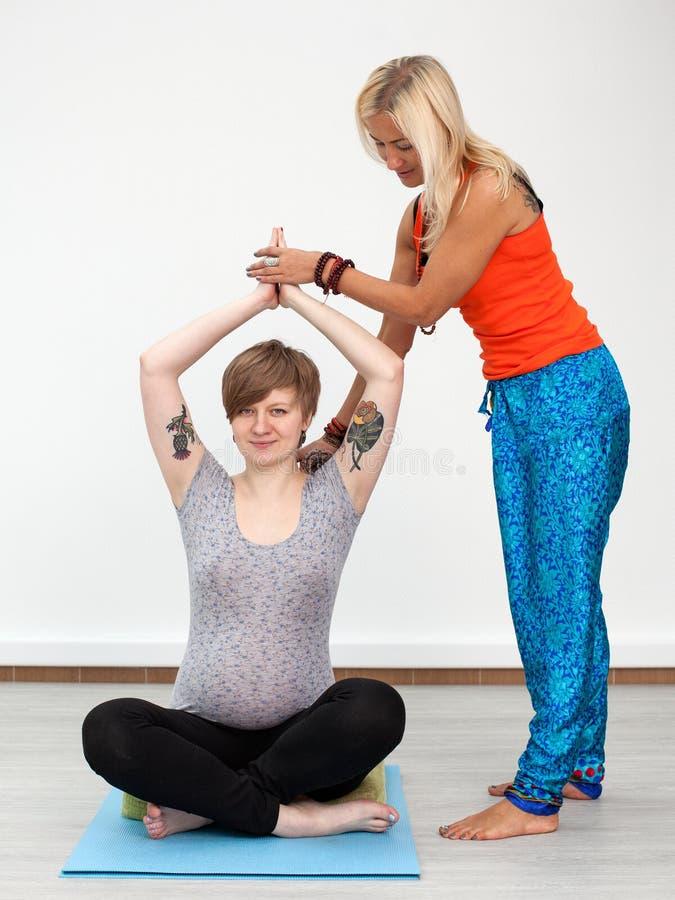妇女辅导员帮助年轻孕妇 免版税库存照片