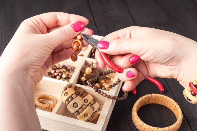 妇女过程手工制造设计自由职业者的工作在家做辅助部件耳环,装饰品 库存图片