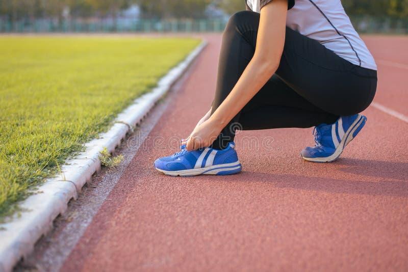 妇女运动为室外跑步或的奔跑,赛跑者妇女栓做准备在跑鞋的鞋带 免版税图库摄影