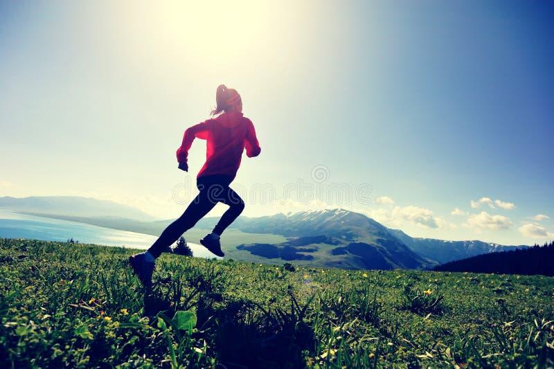 妇女运行在美好的山峰的足迹赛跑者 免版税图库摄影