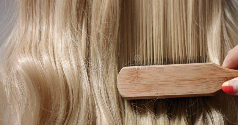 妇女运行通过头发的` s手 库存图片
