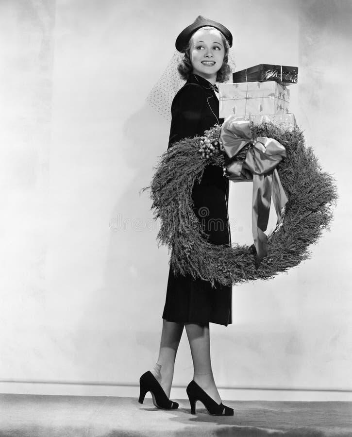 妇女运载的包裹和圣诞节花圈(所有人被描述不更长生存,并且庄园不存在 供应商warrantie 免版税库存图片
