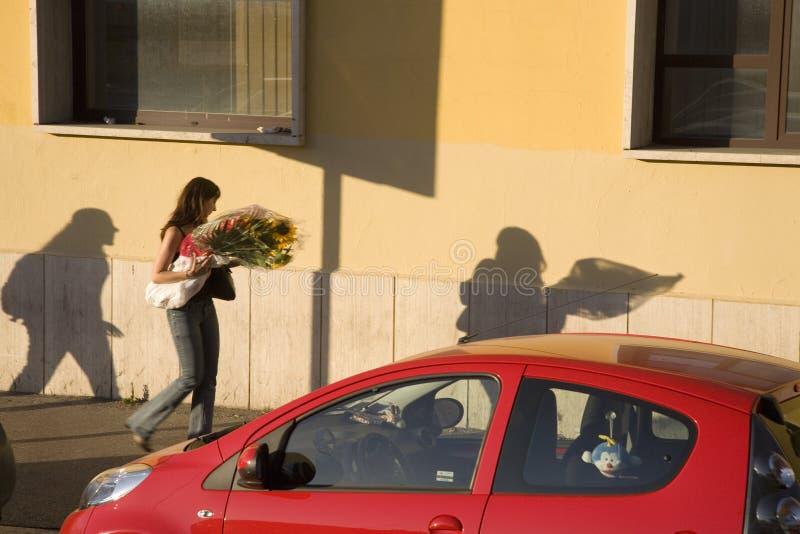 妇女运载的花的长的阴影在罗马意大利临近红色汽车 免版税图库摄影