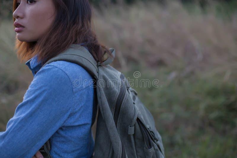 妇女运载的袋子领域日落的旅客 免版税库存图片