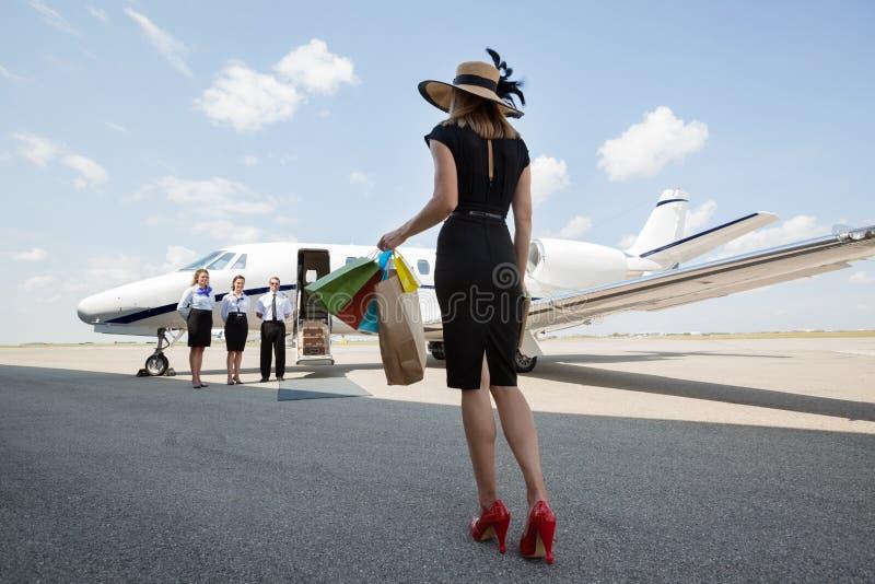 妇女运载的购物袋,当走往时 免版税库存照片