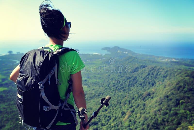 妇女远足者享受在山上面岩石的看法 库存图片