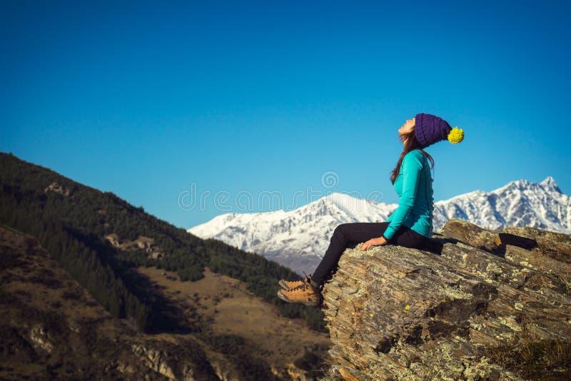 妇女远足者享受在峭壁的阳光 免版税库存图片