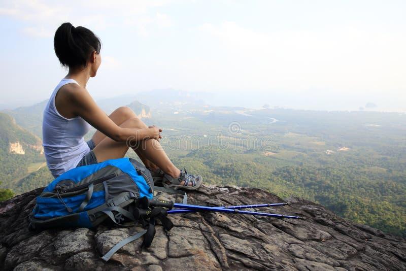妇女远足者享受看法在山峰峭壁 库存图片