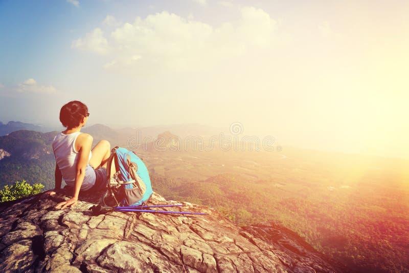 妇女远足者享受看法在山峰峭壁 免版税库存图片