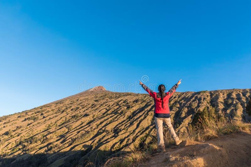 妇女远足者传播的手,享用和满意对山顶视图在完成上升以后在登上Rinjani 免版税库存图片