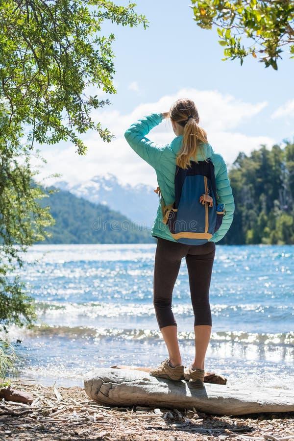 妇女远足者在湖的海岸站立 库存图片