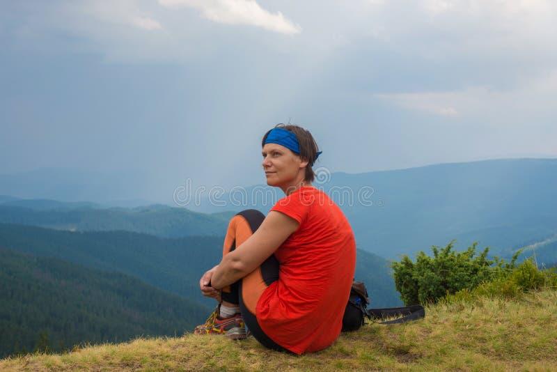 妇女远足者坐在峭壁边缘并且享受看法 免版税库存图片