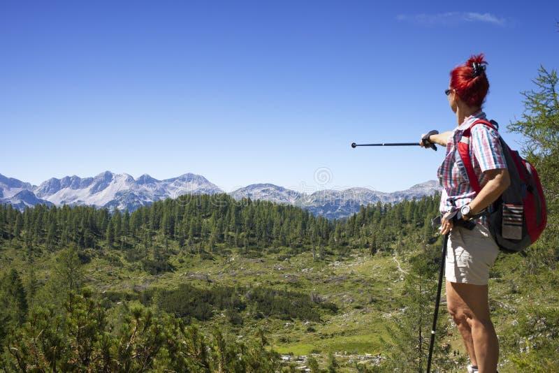 妇女远足者显示山峰 免版税图库摄影