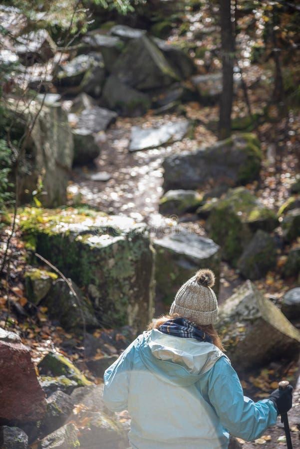 妇女远足艰难在粗糙的地面在秋天 图库摄影
