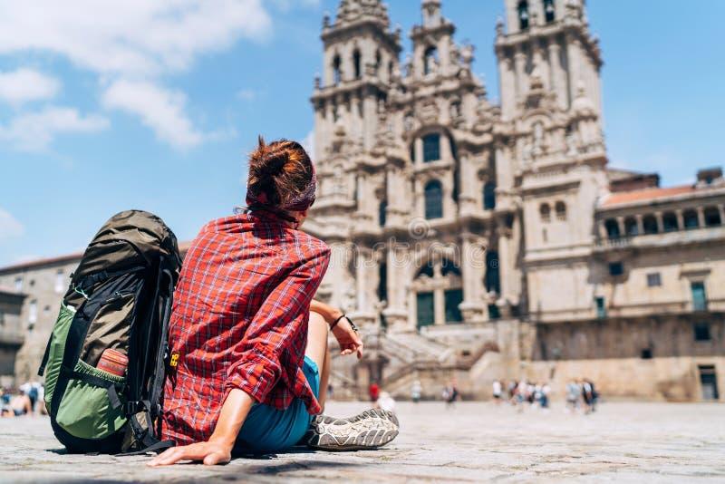 妇女选址在Obradeiro广场广场的背包徒步旅行者piligrim在圣地亚哥-德孔波斯特拉 免版税库存照片