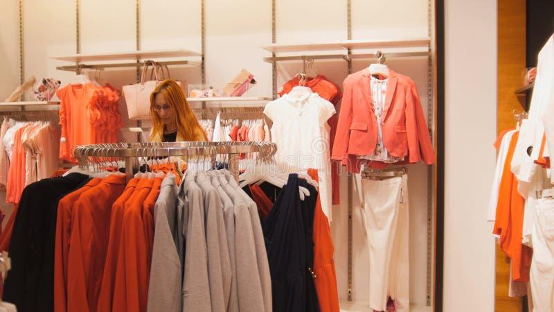妇女选择在妇女` s服装店的一套衣服 免版税库存图片