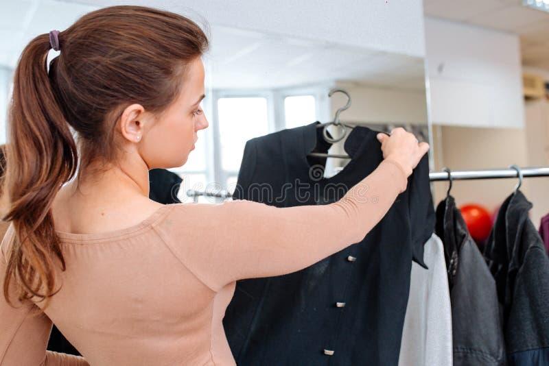 妇女选择在挂衣架的衣裳 免版税库存图片