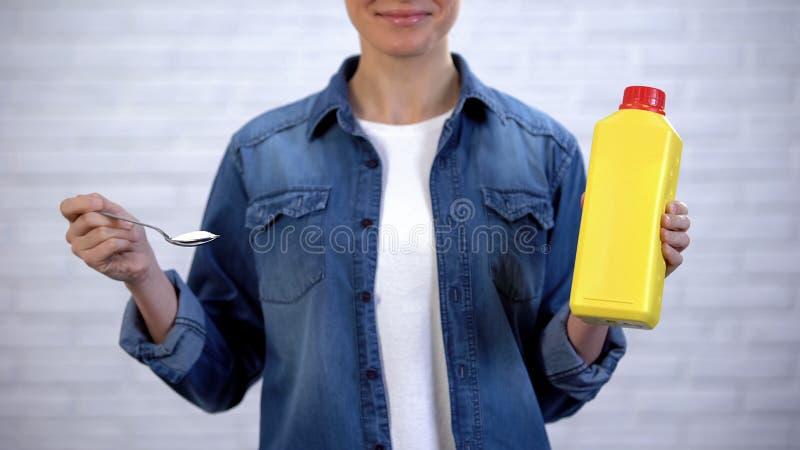 妇女选择在苏打和化工洗涤剂之间的,有机擦净剂概念 免版税图库摄影