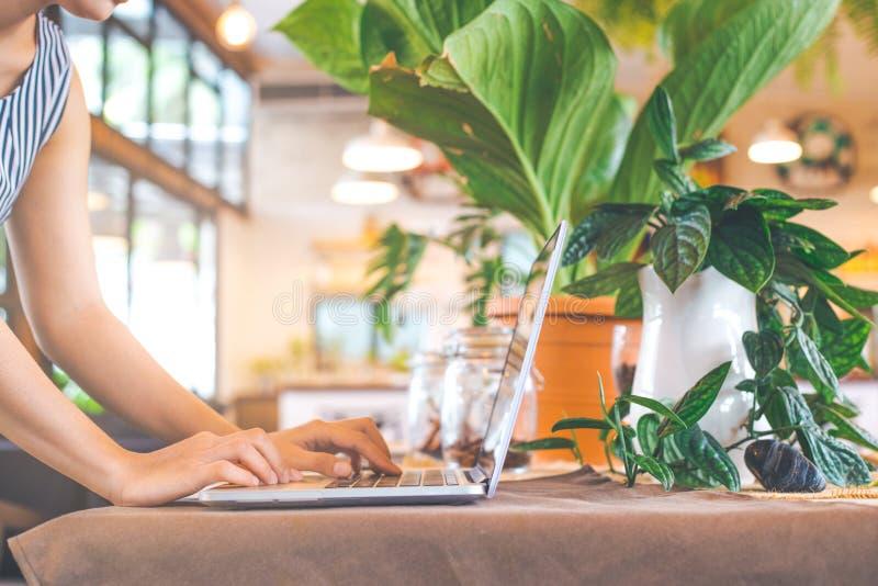 妇女递与在咖啡馆的便携式计算机一起使用 库存图片