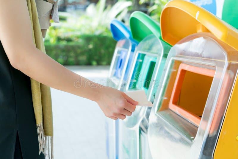 妇女递丢掉垃圾对容器/垃圾,排序废物/垃圾在下落前对容器 库存照片