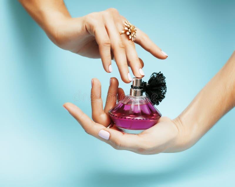 妇女递举行瓶香水桃红色修指甲和首饰在蓝色背景,豪华概念 免版税库存图片