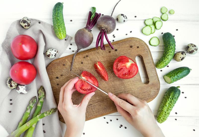 妇女递切在木切板的蕃茄,围拢由菜 平的位置,顶视图 免版税库存照片