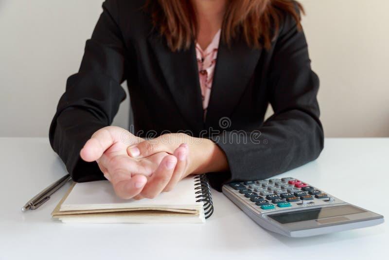 妇女递在书桌办公室综合症状概念的痛苦与笔记本a 免版税库存照片