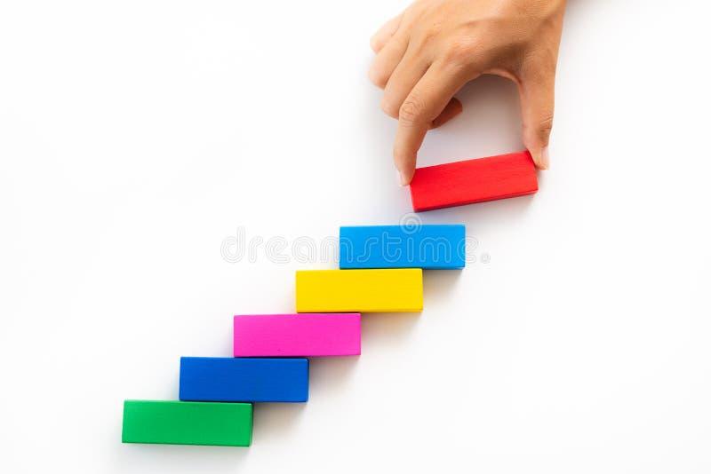 妇女递在五颜六色的木块的被投入的红色木块以楼梯的形式 库存照片