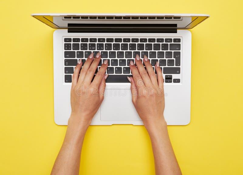 妇女递在站立在黄色背景的膝上型计算机的打印 免版税库存图片