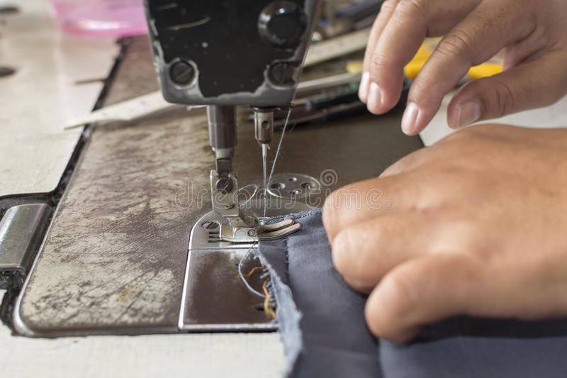 妇女递在缝纫机的被缝合的织品修理在缝合 库存照片