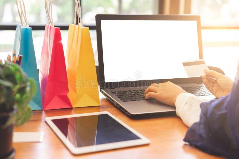 妇女递在网上支付与信用卡和白色屏幕膝上型计算机大模型 库存图片