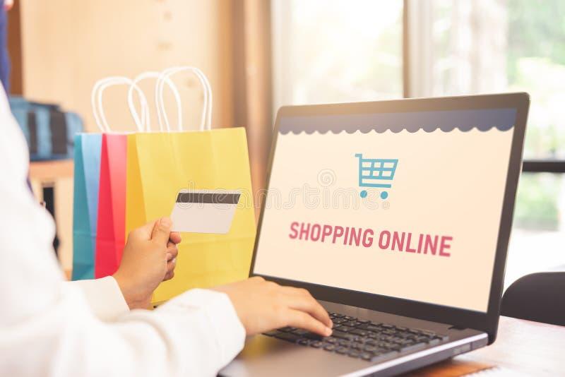 妇女递在网上支付与信用卡和购物的网上屏幕膝上型计算机 免版税库存照片