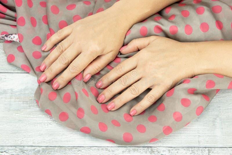 妇女递在钉子修剪的桃红色拿着一条精密明亮的围巾 免版税库存照片