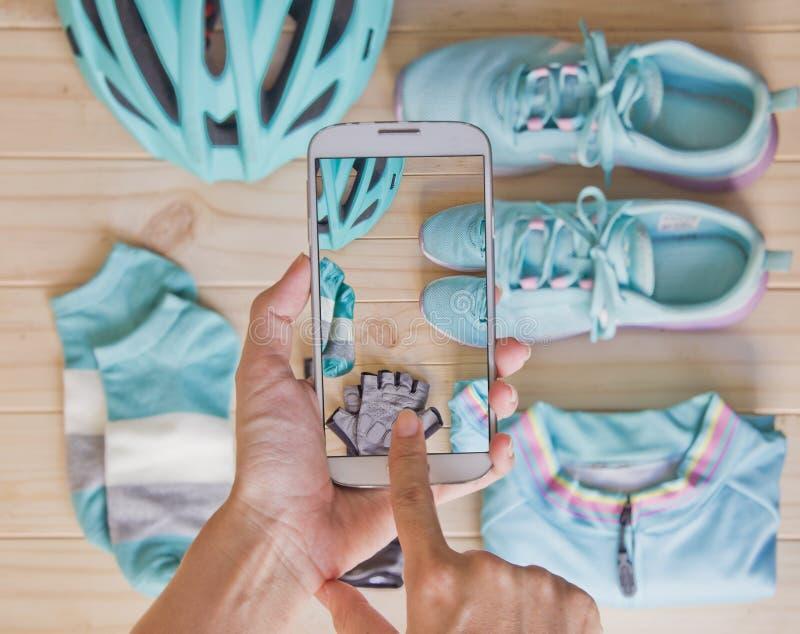 妇女递拍运动器材顶视图照片在淡色的由手机 库存照片
