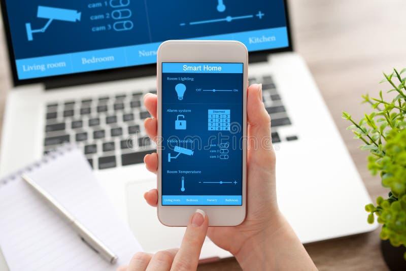 妇女递拿着电话和笔记本有app聪明的家的 免版税图库摄影