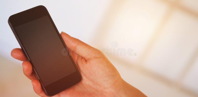 妇女递拿着黑智能手机 库存照片
