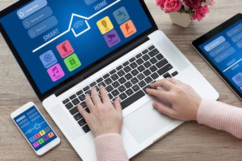 妇女递笔记本计算机片剂电话app聪明的家 免版税库存图片