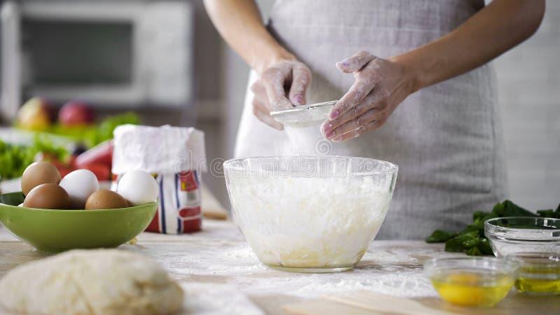 妇女递筛在玻璃碗的面粉用面团,增加烘烤成份 免版税图库摄影