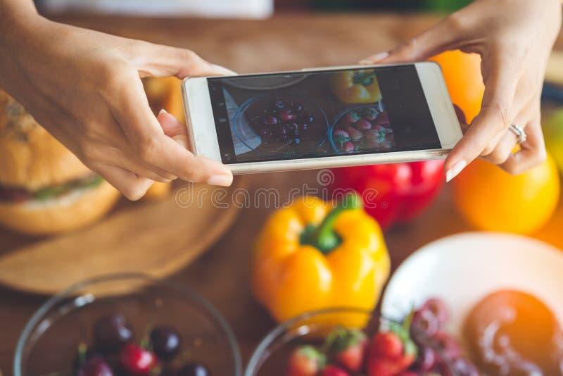 妇女递采取与智能手机,生活方式concep的照片果子 库存照片