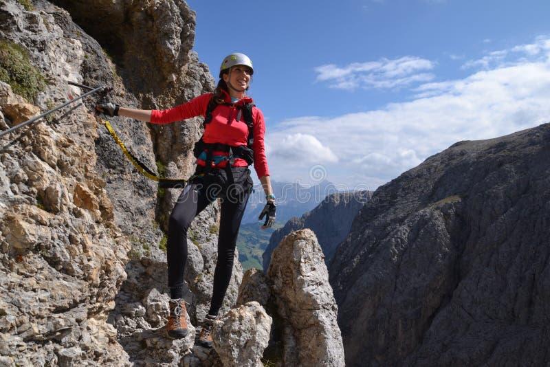 妇女通过在山的ferrata 免版税库存照片