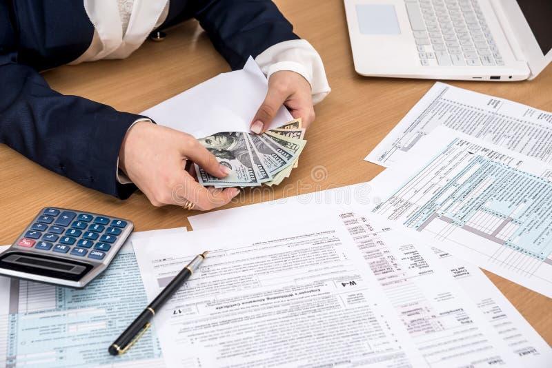 妇女通过填装计数金钱以报税表 免版税图库摄影
