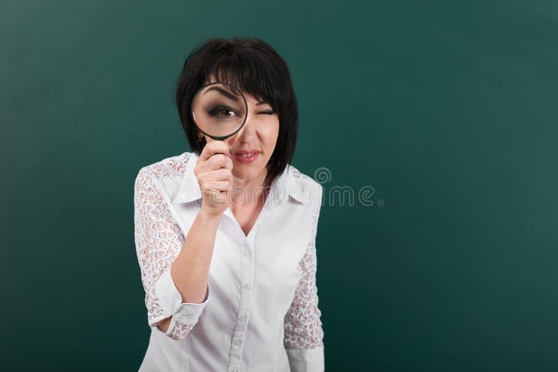 妇女通过放大镜,一个黑板今后看作为背景,大眼睛是可看见的在放大器,概念里面 库存照片