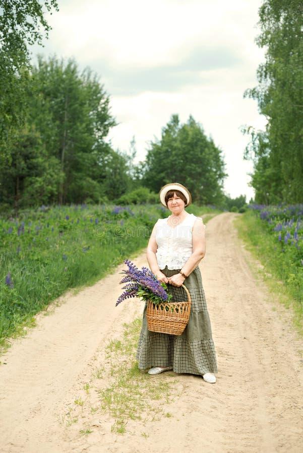 妇女通过森林走停放与与凶猛花花束的一个柳条筐  免版税库存图片