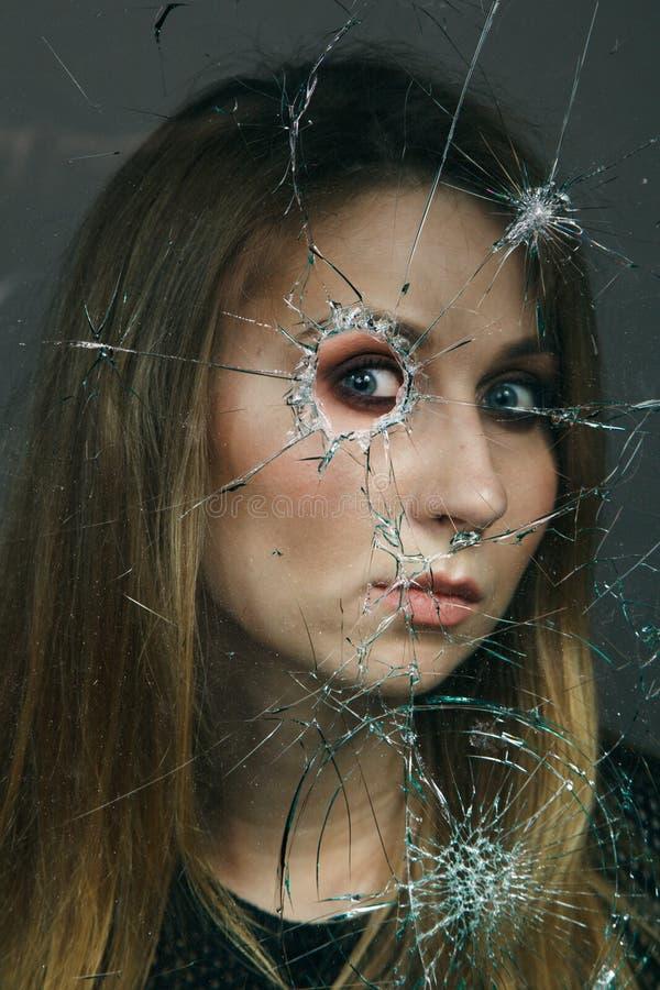 妇女通过残破的玻璃看 接近的纵向 免版税库存照片