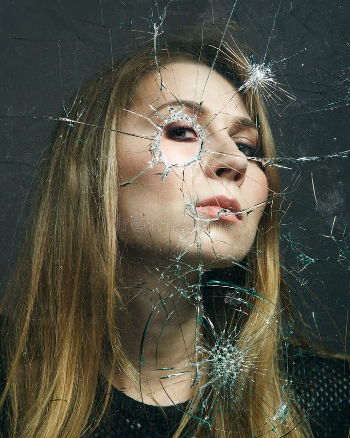 妇女通过残破的玻璃看 接近的纵向 库存照片