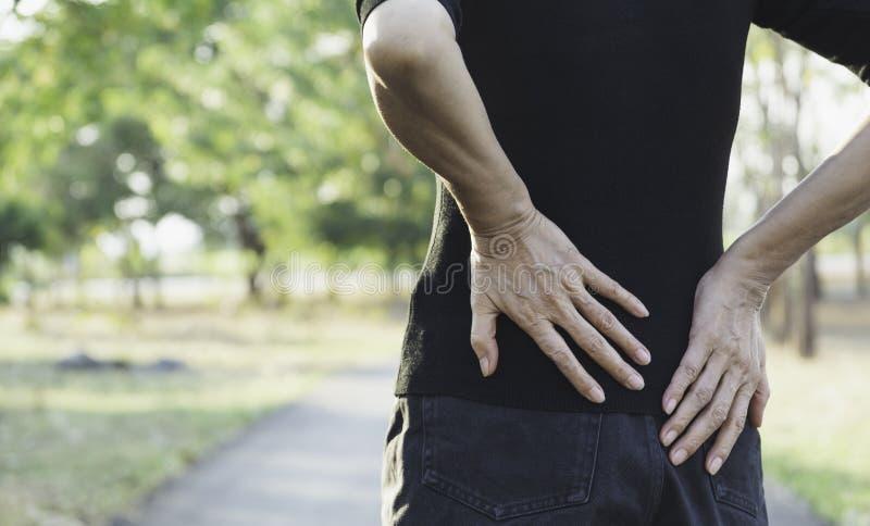 妇女遭受腰疼的,脊骨伤和肌肉发布问题在室外 库存照片