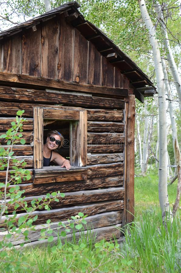 妇女都市探险家微笑通过在一栋老原木小屋的一个残破的窗口在矿工使怀俄明高兴 库存照片