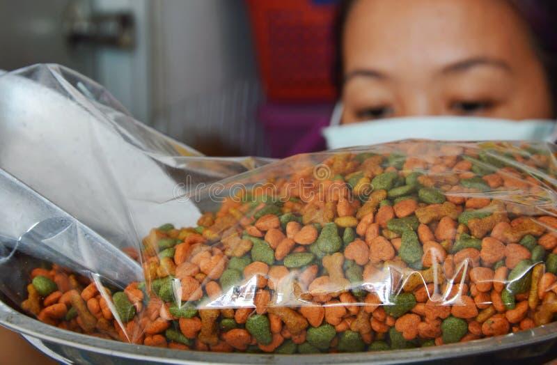 妇女重量在塑料袋的狗食包装的 免版税库存照片