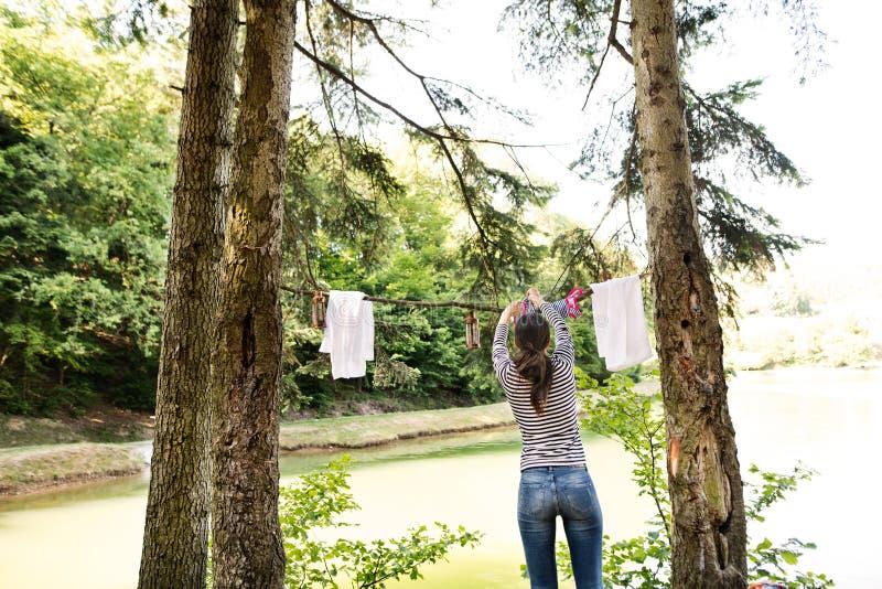 妇女野营假日在湖的森林里 免版税库存照片
