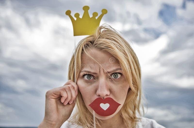 妇女金发举行纸板冠状头饰或冠和爱天空背景的红色嘴唇标志 嬉戏的公主 ?? 库存图片